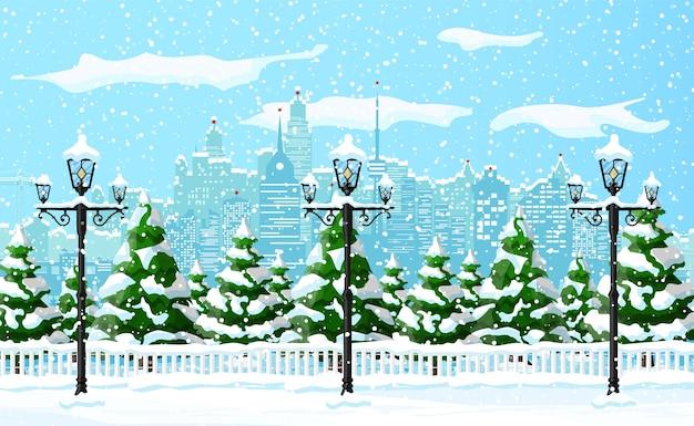 クリスマスの冬の街並み、雪片、木々。都市公園の雪の路地と建物。