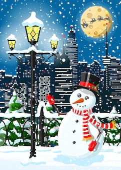 Christmas winter cityscape, snowman and trees. city park snow alley and buildings.