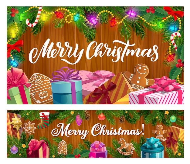 Рождественские подарки и рождественские елки на деревянных фоне. подарите коробки с лентами и бантами, конфетами, звездочками и пряниками, ветками сосны и падуба с носком, шарами, огоньками.