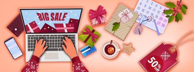 職場の上面図、プレゼント、ラップトップ、手、カレンダーとクリスマス冬のオンラインショッピングの背景