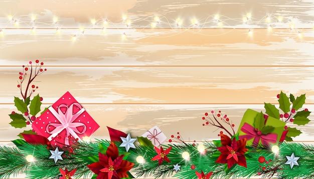 Рождественский зимний фон пуансеттия с подарочными коробками, еловая ветка, ягоды на поверхности деревянного стола