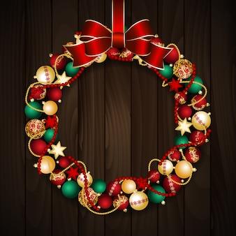 赤いリボンの結び目が付いた赤と金のクリスマスボールからのクリスマスリースの装飾。