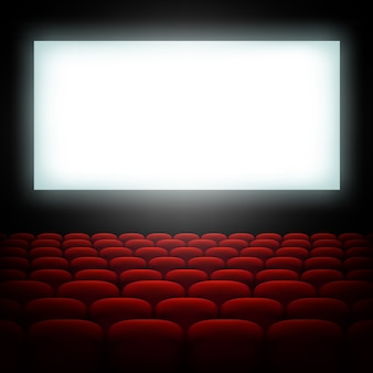 Кинозал с экраном и красными сиденьями.