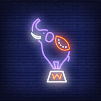 Circus elephant neon icon. trained animal on stand on dark brick wall background.