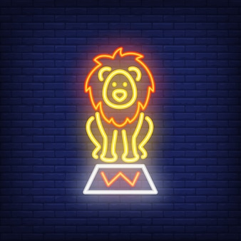 Circus lion neon icon. trained wild animal on stand on dark brick wall background
