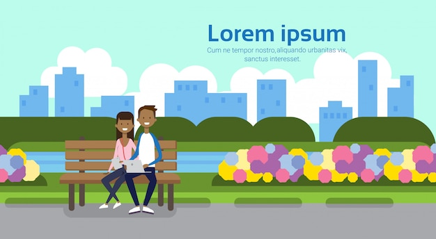 City park african couple man holding laptop woman sitting wooden bench green lawn flowers trees cityscape template background copy space horizontal flat