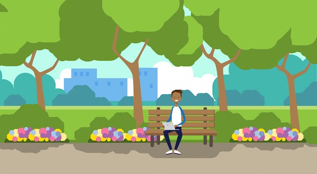 City park african man holding laptop sitting wooden bench green lawn flowers trees cityscape template background horizontal flat
