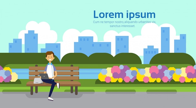 City park man holding laptop sitting wooden bench green lawn flowers trees cityscape template background copy space horizontal flat