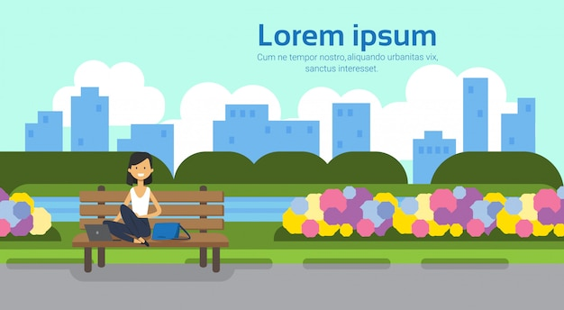 City park woman holding laptopn sitting wooden bench green lawn flowers trees cityscape template background horizontal copy space flat