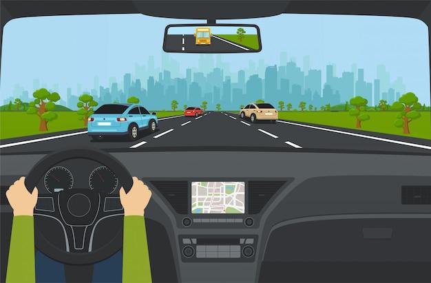 車のダッシュボードと高層ビルと郊外の背景の山々、丘のある近代的な都市のパノラマビューと高速道路の都市交通。都市に通じる車のある道路。