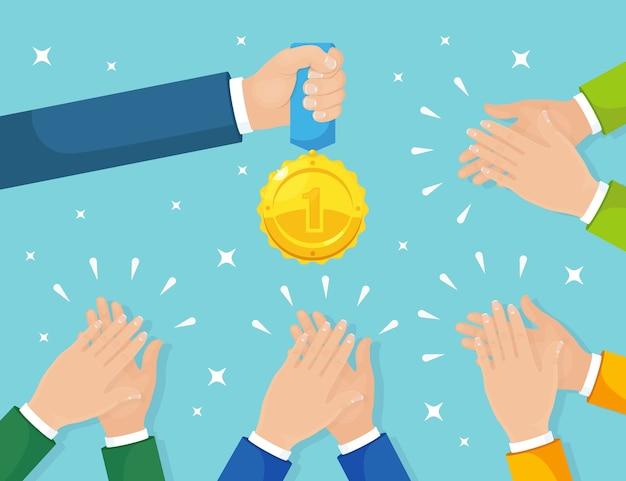 Хлопок в ладоши на фоне. бизнесмен хлопает победителю. мужчина держит золотую медаль. аплодисменты, ура. хорошее мнение, отзывы положительные. поздравляю с удачной сделкой