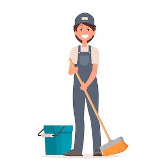 제복을 입은 청소기 여자는 바닥을 청소합니다.