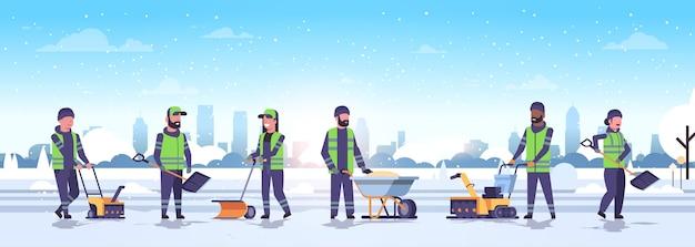 다른 장비와 도구를 사용하여 청소기 팀 눈 제거 겨울 거리 청소 서비스 개념 남성 여성 유니폼 도시 눈 덮인 공원 풍경 평면 전체 길이 수평 벡터 illu