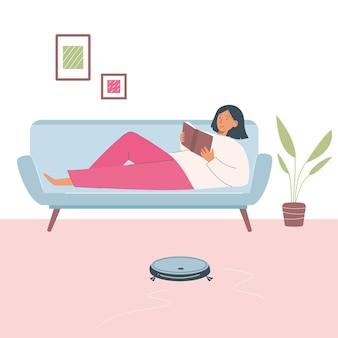 청소 로봇은 여자가 쉬고 책을 읽는 동안 방의 바닥을 청소합니다. 진공청소기 로봇. 집에 대한 기술, 청소 장치.