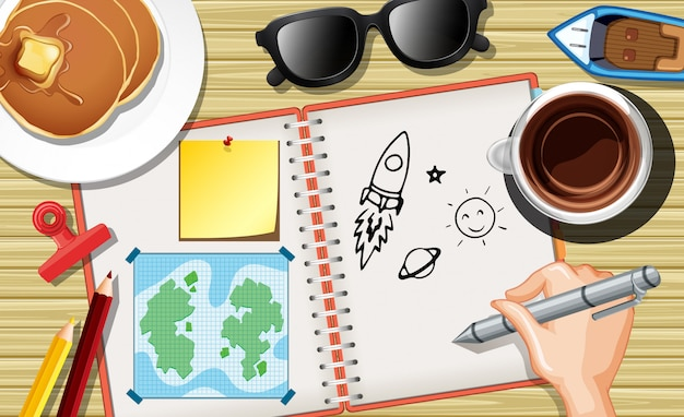 Close up hand writing spaceship on notebook with pancake and coffee cup on desk background