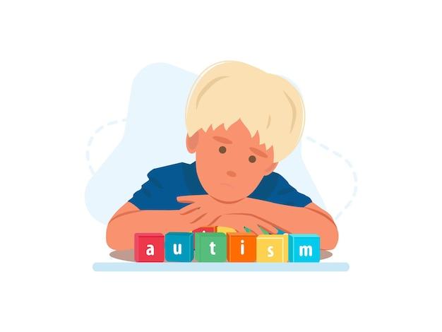 木製のブロックに自閉症という言葉で幼児自閉症の少年の肖像画をクローズアップ