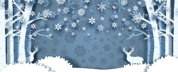 鹿と松林のクローズアップと作物の冬の季節、シルエットの雪の結晶パターンと青い背景のテキストのためのスペース。ペーパーカットスタイルとバナーデザインのクリスマスグリーティングカード。