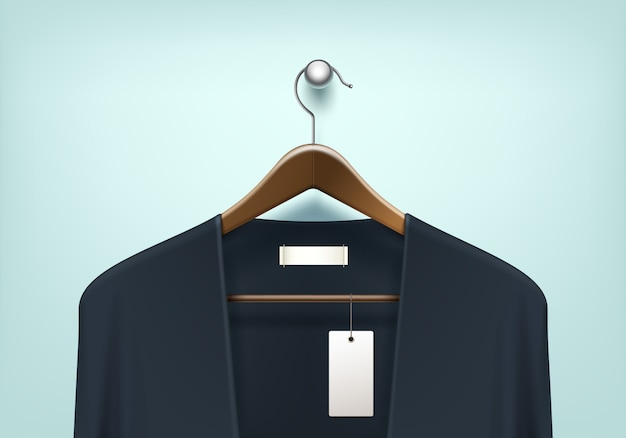 Clothes coat brown wooden hanger with blue black sweater cardigan jumper with blank tag label close up isolated on background