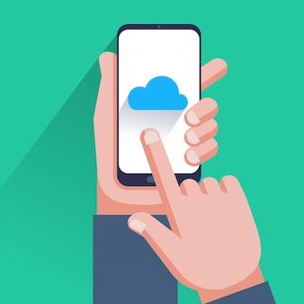 スマートフォンの画面上のクラウドアイコン。スマートフォンを持っている手、画面に触れる指