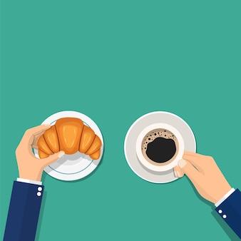 커피와 크루아상, 손 남자. 크로와상을 손에 들고. 아침밥