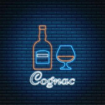벽돌 배경에 네온 스타일의 글자가 있는 코냑 병 및 유리. 알코올 칵테일 바 기호, 로고, 간판.