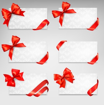 Collection of gift cards with red ribbons.  background