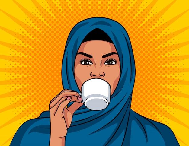 ポップなアートスタイルのカラーイラスト。彼女の頭の上の伝統的なショールで美しいイスラム教徒の女性がコーヒーを飲んでいます。アラビアの女性は彼女の手で一杯のコーヒーを保持します
