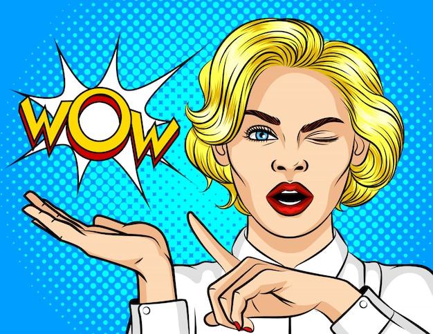 Цветные векторные иллюстрации поп-арт девушка подмигивает и указывает пальцем в сторону. вау эффект. девушка удивлена. шокированная девушка указывает на пузырь со словом вау.