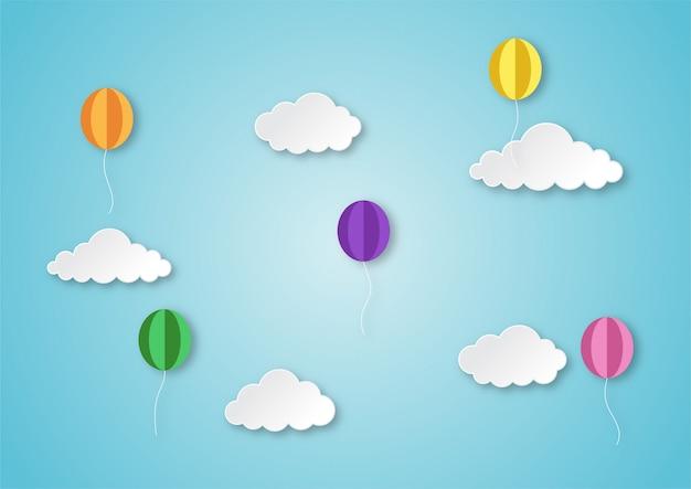 カラフルな風船が雲紙アートスタイルの背景と空を飛んでいます。
