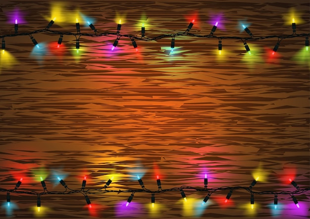 Colorful christmas led lights with glowing effect over wood background