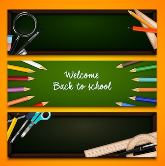 Colorful crayons and school supplies on chalkboard