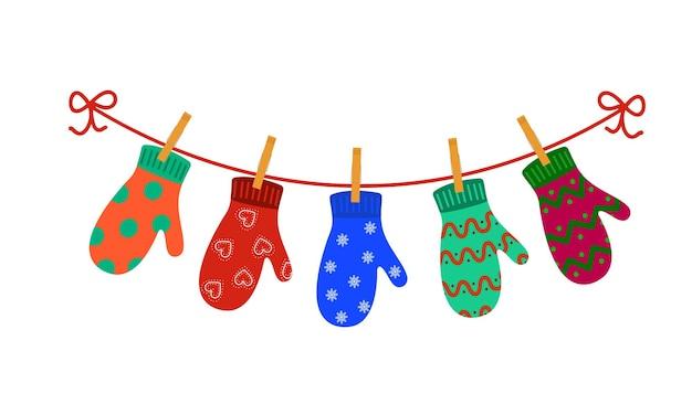 Красочные перчатки, висящие на прищепках на бельевой веревке концепция счастливых зимних праздников