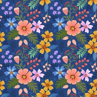 カラフルな手描きの花は、ファブリックテキスタイルの壁紙の青い色のシームレスなパターンに描かれています。