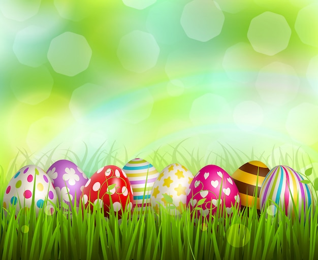Colorful painted easter eggs on green grass on blurred  with bokeh realistic