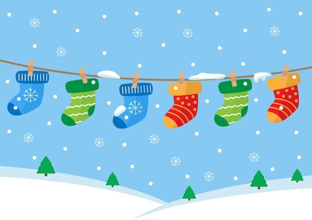 Красочные пары носков висит на веревке. зимний пейзаж