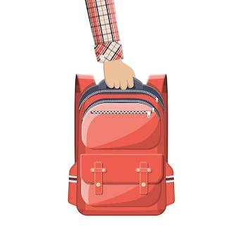 手にカラフルな学校のバックパック。