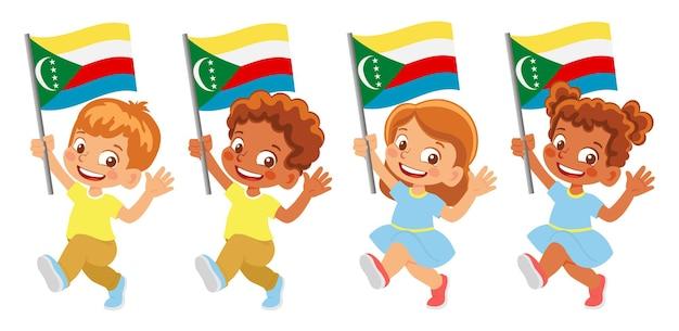 Флаг коморских островов в руке. дети держат флаг. государственный флаг коморских островов