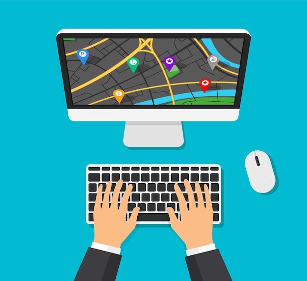 화면에지도 탐색 기능이있는 컴퓨터 모니터. 핀 포인트가 다른 gps 네비게이터. 남자는 컴퓨터 키보드에 입력하고 경로를 만들고 있습니다.
