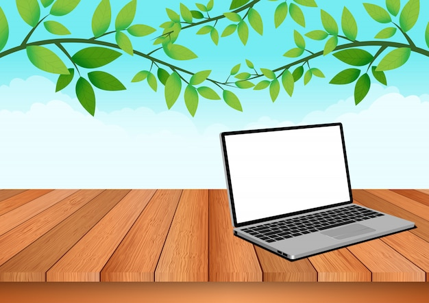 Computer notebook is placed on a wooden floor with natural sky and foliage