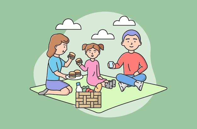 가족 공동 지출 시간의 개념. 피크닉에서 행복한 가족 휴식. 담요에 앉아 햄버거를 먹는 사람들은 휴가에 함께 즐거운 시간을 보냅니다. 만화 선형 개요 평면 벡터 일러스트 레이 션.