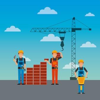 建設労働者の壁のレンガのジャックハンマーとクレーン