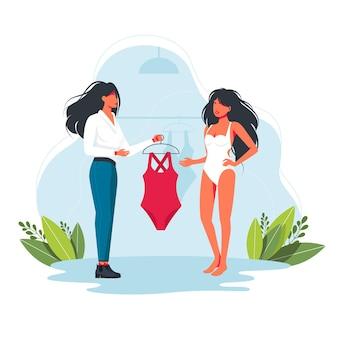 Консультант дает женщине примерить купальник. персональный стилист. женщина примеряет одежду с консультантом по моде. друг женщина и мужчина вместе покупают купальник, вектор. концепт модного бутика