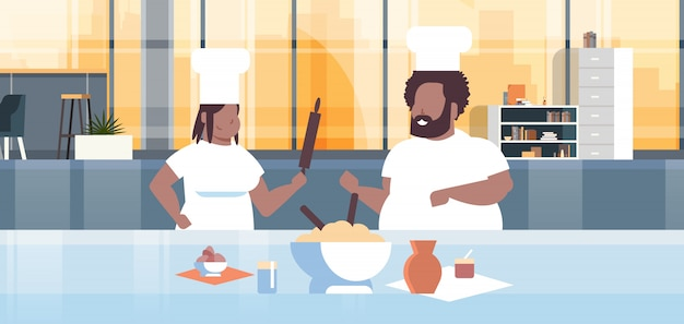 Cooks couple preparing tasty meals   man woman chefs in uniform cooking together modern kitchen
