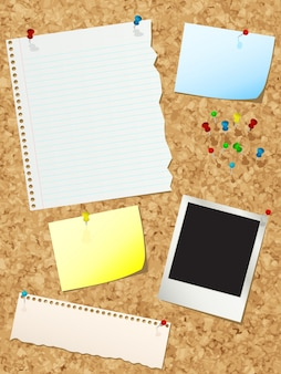 Cork noticeboard with various bits of paper and push pins
