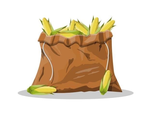 Кукурузные початки с желтыми зернами и зелеными листьями в холщовой сумке.