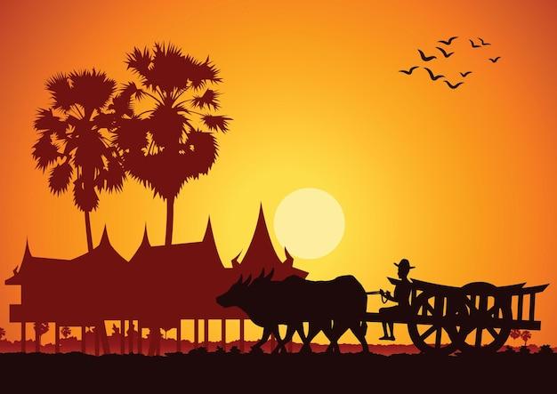 Сельская жизнь азии фермер едет на тележке, чтобы пойти на работу, время восхода солнца, силуэт