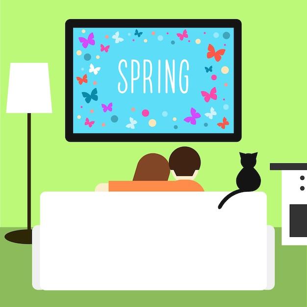커플과 고양이가 방에 있는 소파에 앉아 텔레비전을 보고 있다