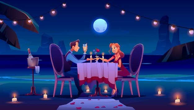 夜のビーチでのカップルはロマンチックなデートのディナーを持っています