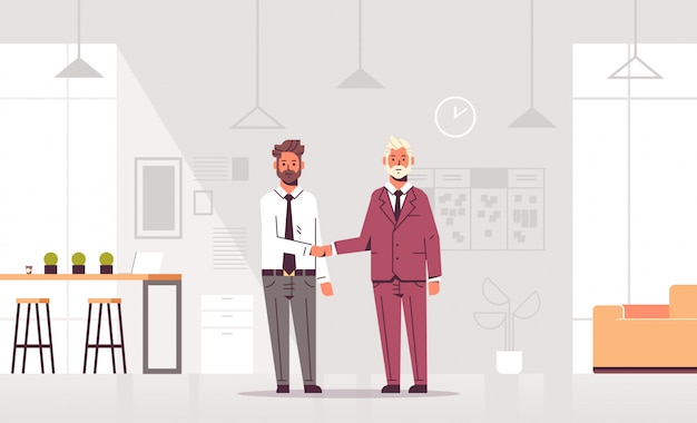 共同ビジネスセンターのモダンなオフィスのインテリアに立っている合意パートナーシップの同僚の会議中にカップルビジネスマンハンドシェイクビジネスパートナーの手ふれ