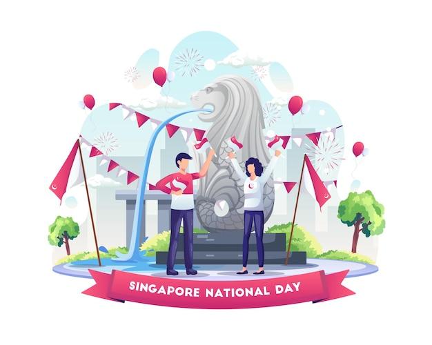 ライオン像のイラストの前で8月9日にシンガポールの独立記念日を祝うカップル